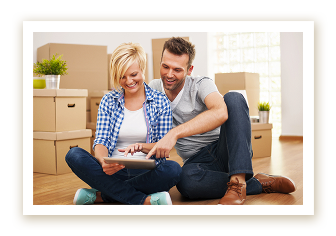Couple looking at tablet surrounded by boxes